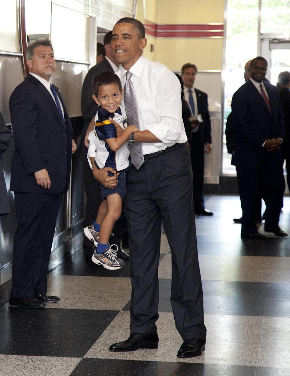 President Barack Obama picks up a boy as he visits The Varsity restaurant, Tuesday, June 26, 2012, in Atlanta. (AP Photo/Carolyn Kaster)