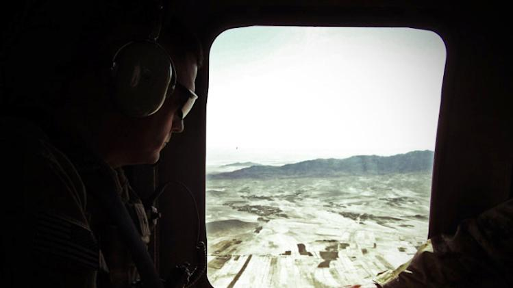 This photo taken Oct. 10, 2012 shows Army Brig. Gen. John Charlton, left, riding in a Blackhawk helicopter in eastern Afghanistan. A new chapter of the Afghanistan war is opening with a slimmed-down Western force doing more advising than fighting, a resilient Taliban showing little interest in peace talks, and Americans tempted to pull the plug on a conflict now in its 12th year. A decisive end seems nowhere in sight. (AP Photo/Robert Burns)