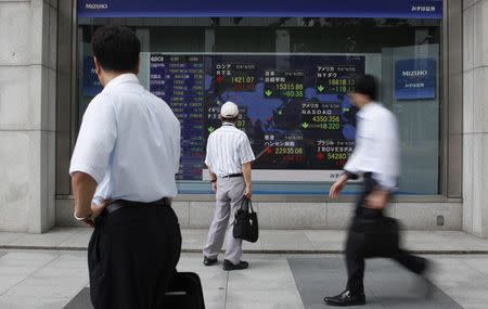 Pedestrians look at an electronic board showing the stock market indices of various countries outside a brokerage in Tokyo