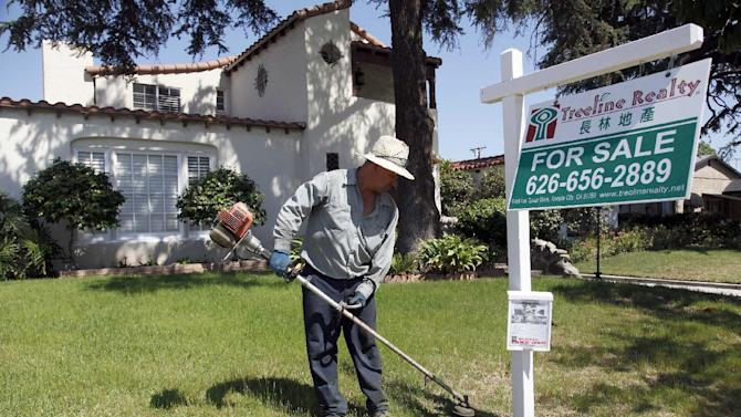 In this Monday, May 13, 2013 photo, gardener Jose Lopez trims the front lawn of a home for sale in Alhambra, Calif.  Freddie Mac reports on mortgage rates for the week on Thursday, May 23, 2013. (AP Photo/Nick Ut)