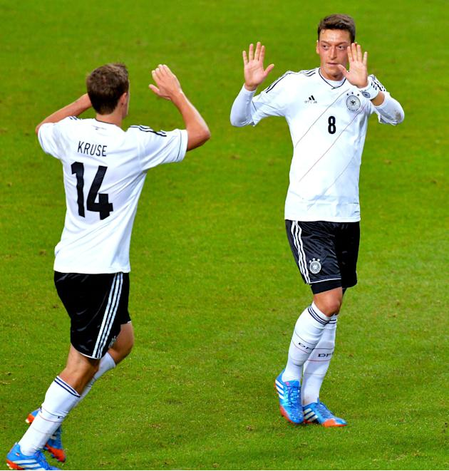 Germany's Mesut Ozil, right, celebrates scoring his team's first goal with team mate Max Kruse during the 2014 World Cup group C qualifying soccer match between Sweden and Germany at Friends Arena in