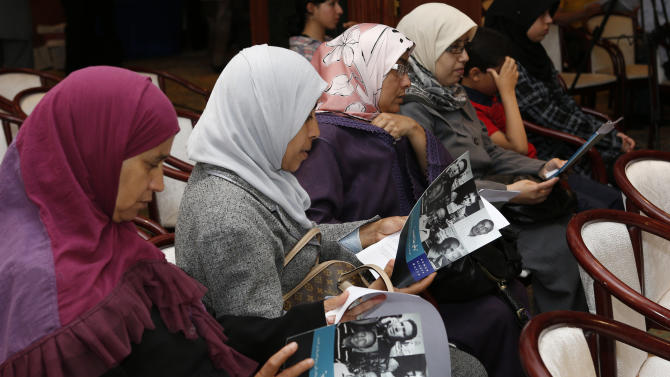 "Relatives of victims look at Human Rights Watch new report ""Just sign here"" before a news conference in Rabat, Morocco, Friday, June 21, 2013. Human Rights Watch says in a new report that Morocco's justice system overly relies on coerced confessions and needs serious reform. (AP Photo/Abdeljalil Bounhar)"