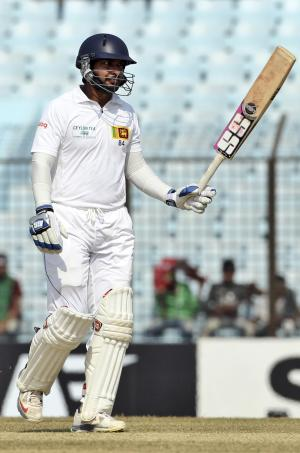 Sri Lanka's Kumar Sangakkara acknowledges the crowd after scoring a century on the fourth day of the second test cricket match against Bangladesh in Chittagong, Bangladesh, Friday, Feb. 7, 2014. (AP Photo)