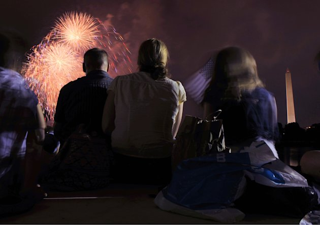 A family watches  from the Jefferson Memorial as fireworks explode over Washington Monday, July 4, 2011, during the annual Fourth of July display. (AP Photo/Cliff Owen)