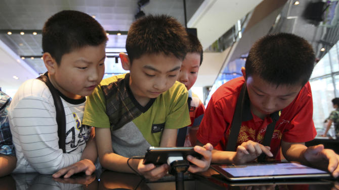 Chinese children try out Galaxy products at Samsung's showroom in Seoul, South Korea, Friday, July 6, 2012. Samsung Electronics Co., the world's largest maker of memory chips, mobile phones, flat-screen panels and televisions, said Friday that its preliminary second-quarter operating profit jumped nearly 80 percent from a year ago to a record high. Analysts said the sharp rise was driven by Galaxy smartphone sales. (AP Photo/Hye Soo Nah)