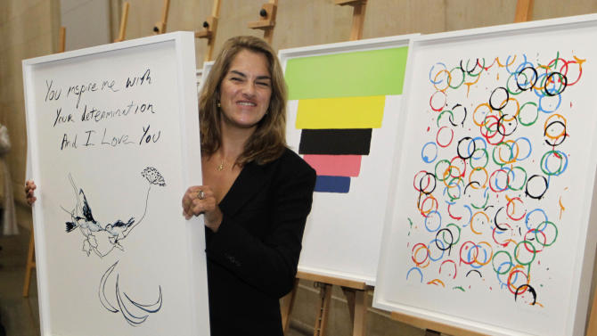 British artist Tracey Emin poses with her Paralympic poster 'Birds 2012' during an unveiling ceremony of London 2012 Olympic and Paralympic posters at the Tate Britain art gallery in London, Friday, Nov. 4, 2011. Olympic officials on Friday unveiled the posters for the London 2012 games, which highlight 12 different takes on how to celebrate the Olympic and Paralympic games. (AP Photo/Sang Tan)