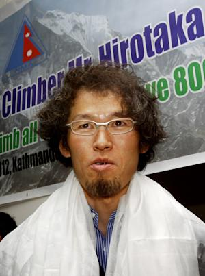 Japanese climber Hirotaka Takeuchi stands in front of a banner after he was felicitated by the President of Nepal Mountaineering Association Zimba Zangbu Sherpa, in Katmandu, Nepal, Sunday, June 10, 2012. Takeuchi climbed a Himalayan peak Mount Dhaulagiri 8,167 meters (26,788 feet) high in Nepal to become the first person from his country to scale the 14 tallest mountains of the world, mountaineering officials said. (AP Photo/Binod Joshi)