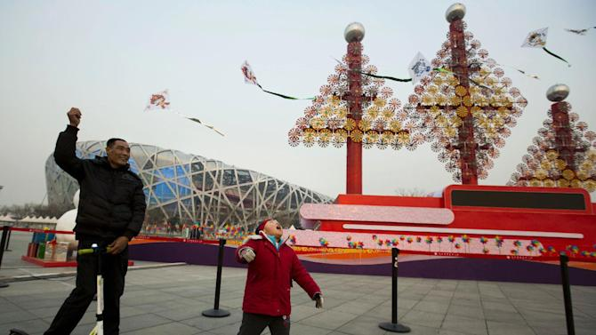 """A man flies a kite for a child near Christmas decorations with the backdrop of the iconic Beijing National Stadium """"Bird's Nest"""" in Beijing, China, Friday, Dec. 26, 2014. (AP Photo/Ng Han Guan)"""