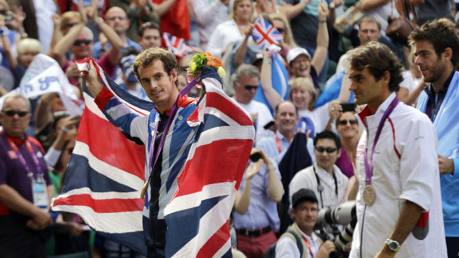 Gold medalist Andy Murray of Great Britain, left, draped in a British flag, walks with silver medalist Switzerland's Roger Federer, second right, and bronze medalist Juan Martin del Potro of Argentina, right, after the medal ceremony of the men's singles event at the All England Lawn Tennis Club at Wimbledon, in London, at the 2012 Summer Olympics, Sunday, Aug. 5, 2012. (AP Photo/Elise Amendola)