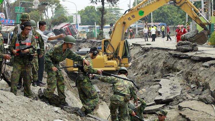 Soldiers use electronic sensors to search for missing persons believed to be buried after massive gas explosions in Kaohsiung, Taiwan, Friday, Aug. 1, 2014. A series of explosions about midnight Thursday and early Friday ripped through Taiwan's second-largest city, killing scores of people, Taiwan's National Fire Agency said Friday. (AP Photo/Wally Santana)