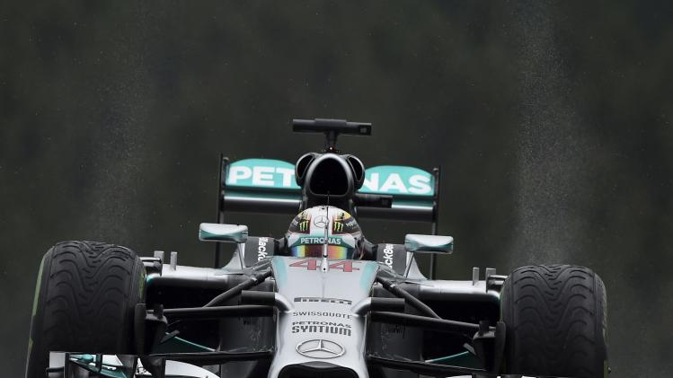 Mercedes Formula One driver Hamilton of Britain drives in the pit lane during the qualifying session at the Belgian F1 Grand Prix in Spa-Francorchamps