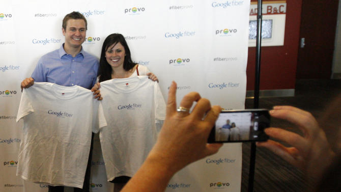 Steven Staples and Whitney Wing pose for photos with their Google Provo shirts after it was announced that Google will make Provo, Utah, the third city to get its high-speed Internet service via fiber-optic cables, Wednesday, April 17, 2013 in Provo. The Provo deal is the first time Google plans to acquire an existing fiber-optic system. The city of 115,000 created the fiber-optic network, iProvo, in 2004, which has struggled to break even. (AP Photo/The Salt Lake Tribune, Rick Egan)  DESERET NEWS OUT; LOCAL TV OUT; MAGS OUT