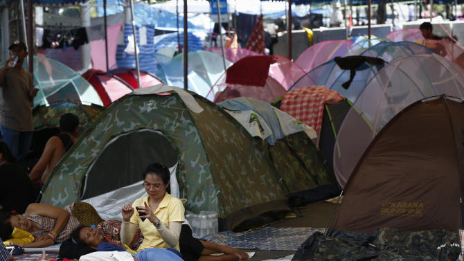 Anti-government protesters rest at a camp site in downtown Bangkok, Thailand, Sunday, May 11, 2014. Thai anti-government protesters who have been camped out in several locations in Bangkok packed their tents as they ramped up their efforts to bring down what remains of Prime Minister Yingluck Shinawatra's administration by laying siege to television stations, surrounding state offices and demanding lawmakers help them install a non-elected prime minister to rule the country. (AP Photo/Vincent Thian)