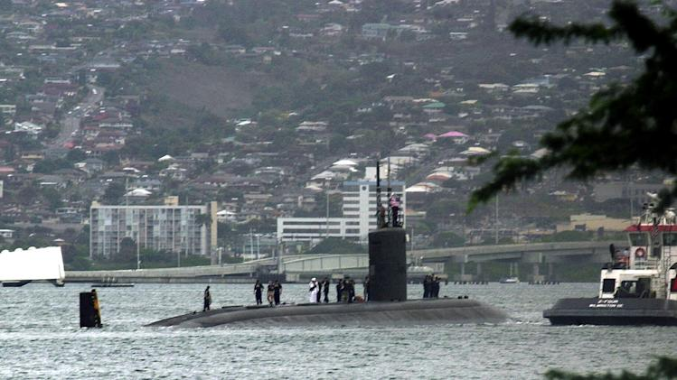 FILE - The submarine USS Greeneville is escorted to the submarine base at Pearl Harbor, in this Feb. 10, 2001, file photo. A high concentration of important military commands and facilities on the island mean there's a great deal of information in Hawaii that potential adversaries want to know. (AP Photo/Ronen Zilberman)