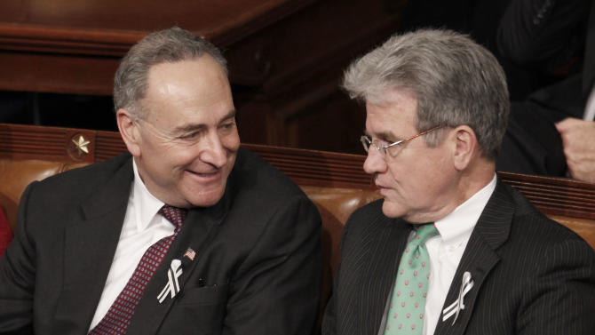 FILE - In this Jan. 25, 2011 file photo, Sen, Charles Schumer, D-N.Y., left, talks with Sen. Tom Coburn, R-Okla., on Capitol Hill in Washington, during President Barack Obama's State of the Union address in Washington. Should veterans deemed too mentally incompetent to handle their own financial affairs be prevented from buying a gun? The issue, for a time last week, threatened to become the biggest sticking point in a $631 billion defense bill for reshaping a military that is disengaging from a decade of warfare. Coburn sought to amend the bill to stop the Veterans Affairs Department from putting the names of veterans deemed too mentally incompetent to handle their finances into the National Instant Criminal Background Check System, which prohibits them from buying or owning firearms. Schumer, objected, saying the measure would make it easier for veterans with mental illness to own a gun, endangering themselves and others. (AP Photo/Evan Vucci, File)