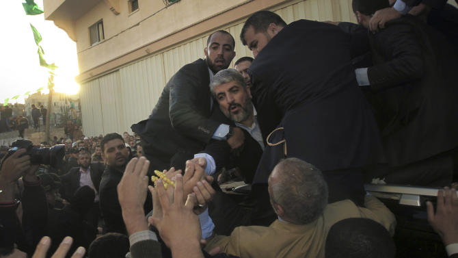 The exiled Hamas chief Khaled Mashaal greets Palestinians as he parades through the streets with Hamas prime minister, not seen, following Mashaal's arrival in Gaza City, Friday, Dec. 7, 2012. Mashaal broke into tears Friday as he arrived in the Gaza Strip for his first-ever visit, a landmark trip reflecting his militant group's growing international acceptance and its defiance of Israel. Khaled Mashaal, who left the West Bank as a child and leads the Islamic militant movement from Qatar, crossed the Egyptian border, kissed the ground, and was greeted by a crowd of Hamas officials and representatives of Hamas' rival Fatah party. (AP Photo/Mahmud Hams, Pool)