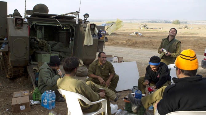 Israeli reserve soldiers gather to drink coffee in a 155 mm artillery position near Israel Gaza Border, southern Israel, Thursday, Nov. 22, 2012. A cease-fire agreement between Israel and the Gaza Strip's Hamas rulers took effect Wednesday night, bringing an end to eight days of the fiercest fighting in years and possibly signaling a new era of relations between the bitter enemies. (AP Photo/Ariel Schalit)