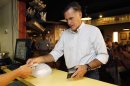 Republican presidential candidate and former Massachusetts Gov. Mitt Romney pays for a pulled chicken sandwich as he campaigns at Stepto&#39;s BBQ Shack in Evansville, Ind., Saturday, Aug. 4, 2012. (AP Photo/Charles Dharapak)