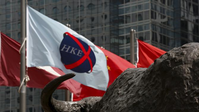 A flag of Hong Kong Stock Exchange flies in front of a buffalo sculpture outside Exchange Square business tower where the Hong Kong Stock Exchange is located