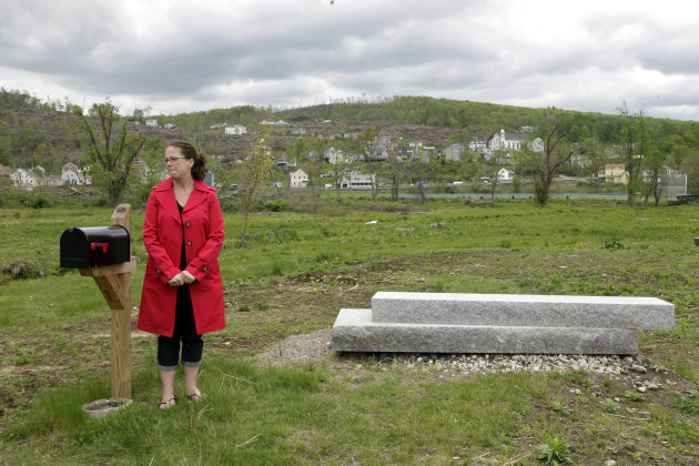 In this May 10, 2012 photo, Pia Rogers stands by her front steps in Monson, Mass., the only part of her house left intact after a year after a tornado blew through central Massachusetts and devastated