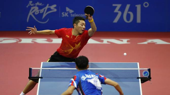 China's Xu Xin returns a shot against South Korea's Lee Jung-woo during their men's team gold medal table tennis match at Suwon Gymnasium, during the 17th Asian Games in Incheon