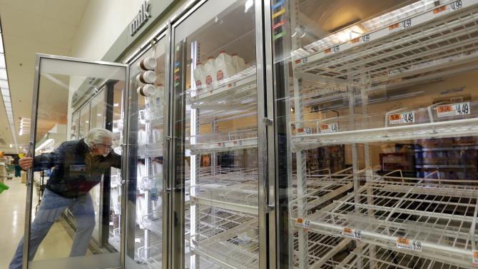 Jack Percoco of Cambridge, Mass. reaches into depleted shelves for milk at a supermarket in Somerville, Mass., Friday, Feb. 8, 2013. A major winter storm is heading toward the U.S. Northeast with up to 2 feet of snow expected for a Boston-area region that has seen mostly bare ground this winter. (AP Photo/Elise Amendola)