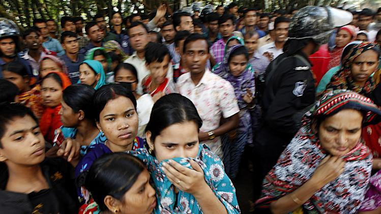 People look at a burnt garment factory outside Dhaka, Bangladesh, Sunday, Nov. 25, 2012. At least 112 people were killed late Saturday night in a fire that raced through the multi-story garment factory just outside of Bangladesh's capital, an official said Sunday. (AP Photo/Hasan Raza)