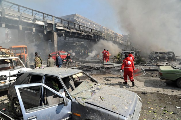 This photo released by the Syrian official news agency SANA, shows first responders working after a huge explosion that shook central Damascus, Syria, Thursday, Feb. 21, 2013. A car bomb shook central