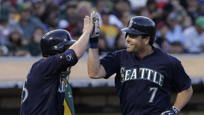 Seattle Mariners' Seth Smith (7) celebrates after hitting a two-run home run off Oakland Athletics pitcher Jesse Chavez that scored Kyle Seager, left, during the sixth inning of a baseball game in Oakland, Calif., Friday, July 3, 2015. (AP Photo/Jeff Chiu)