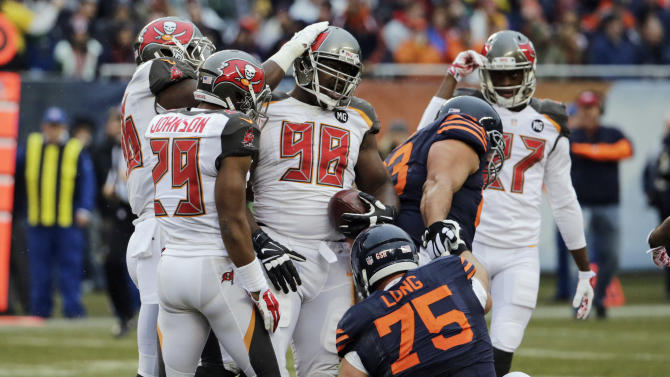 Tampa Bay Buccaneers defensive tackle Clinton McDonald (98) is congratulated by his teammates after recovering a fumble by Chicago Bears quarterback Jay Cutler during the first half of an NFL football game Sunday, Nov. 23, 2014, in Chicago