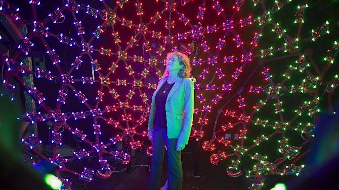"""In this photo taken Tuesday, Jan. 29, 2013, University of Southern California Institute for Creative Technologies manager, Lori Weiss relaxes to music synchronized with color LEDs, inside the Lighting Stage X, the institute's latest LED-filled sphere used to help create realistic virtual characters in Playa Vista area of Los Angeles. The technology is used by the """"Virtual Survivor Visualization,"""" part of a collaboration with the Shoah Foundation to digitize aging Holocaust survivors to create three-dimensional holograms that would not only be able to tell their stories to future generations but to engage in dialogue with them. (AP Photo/Damian Dovarganes)"""