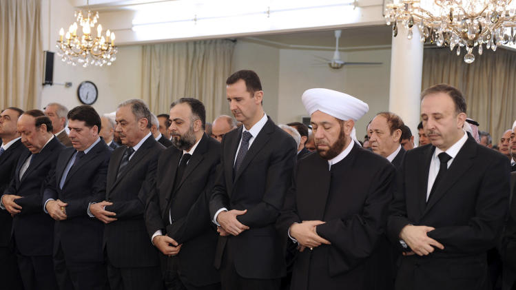 In this photo released by the Syrian official news agency SANA, Syrian President Bashar Assad, center, prays at a mosque on the first day of Eid al-Adha, Friday, Oct. 26, 2012. Fighting raged near a military base in Syria's north as a cease-fire in the bloody civil war was supposed to go into effect Friday at dawn, activists said, illustrating the difficulty of enforcing even a limited truce coinciding with a Muslim holiday. (AP Photo/SANA)