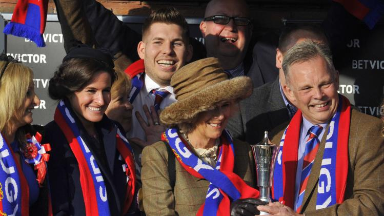 Britain's Camilla, Duchess of Cornwall, has a scarf placed around her by members of the Preston family at the Cheltenham Festival horse racing meet in Gloucestershire