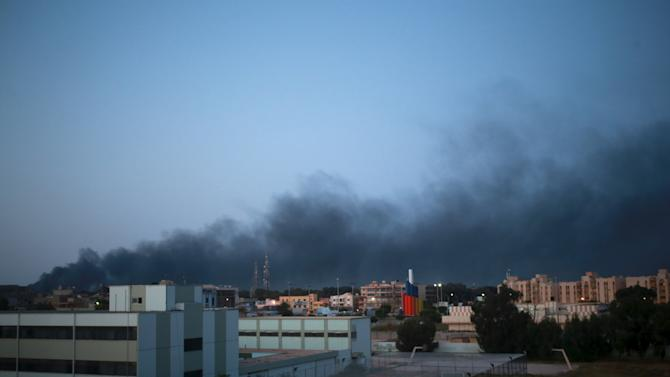 Smoke billows in the sky above areas where clashes are taking place between pro-government forces and the Shura Council of Libyan Revolutionaries in Benghazi