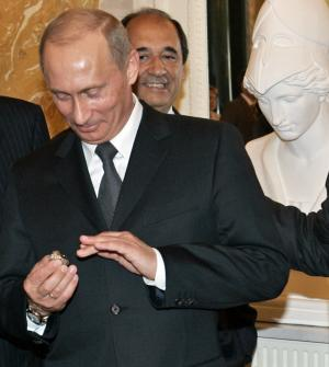 FILE - In this June 25, 2005, file photo, Russian President Vladimir Putin holds a diamond-encrusted 2005 Super Bowl ring belonging to New England Patriots NFL football team owner Robert Kraft during a meeting of American business executives at the 18th century Konstantin Palace outside St. Petersburg, Russia. When Putin arrived in London on Sunday, June 16, 2013, his spokesman was asked about a New York Post story quoting Kraft saying Putin pocketed his Super Bowl ring in 2005. Putin said he's happy to buy New England Patriots' owner Robert Kraft another ring, but it's absurd to suggest he stole the Super Bowl one. (AP Photo/Alexander Zemlianichenko, File)