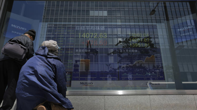 People look at the electronic stock board of a securities firm in Tokyo, Tuesday, May 7, 2013. Japan's benchmark stock index, reopening after a long weekend holiday, surged Tuesday in the wake of a U.S. jobs report issued late last week that handily beat expectations. (AP Photo/Itsuo Inouye)