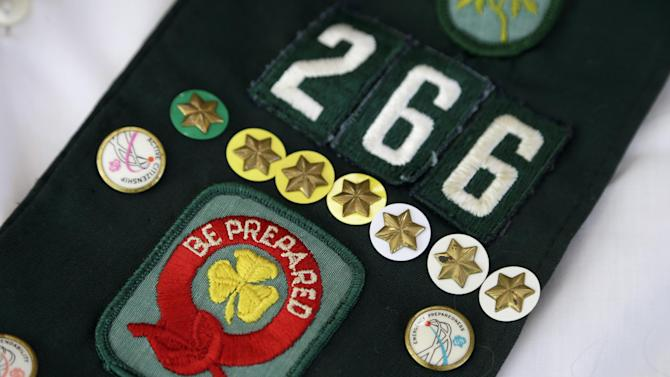 This Tuesday, May 14, 2013 photo shows pins on the childhood Girl Scouts sash of Joni Kinsey, in Iowa City, Iowa. In an effort to save money, Girl Scout councils across the country are making proposals that would have been unthinkable a generation ago: selling summer camps that date back to the 1950s. (AP Photo/Charlie Neibergall)