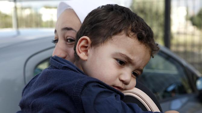 "Bushr Al Tawashi, as he is carried by his mother Arin Al Dakkar, outside of a private Sigma TV station, in Nicosia, Cyprus, Friday, Oct. 26, 2012. A 2-year-old Syrian boy who was believed dead after his family inadvertently left him behind as they fled shelling in Damascus last summer has been reunited with his parents in Cyprus, a lawyer said. ""You can imagine how they felt when they were told their son was alive after bearing all this guilt thinking that he was dead,"" lawyer Stella Constantinou told The Associated Press. (AP Photo/Petros Karadjias)"