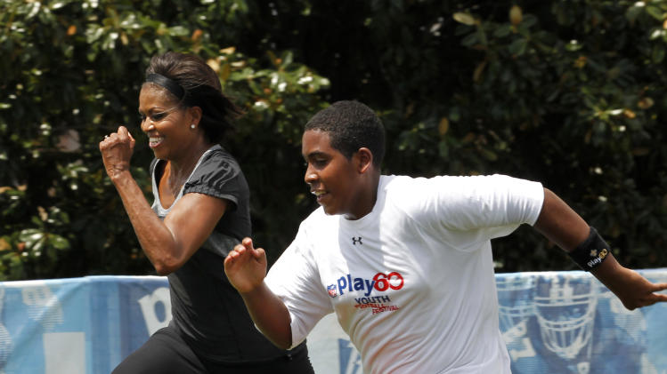 "FILE - In this Sept. 8, 2010, file photo, first lady Michelle Obama runs a 40-yard sprint as she participates in the Let's Move!  Campaign and the NFL's Play 60 Campaign festivities with area youth, to promote exercise and fight childhood obesity in New Orleans. Michelle Obama has a new look, both in person and online, and with the president's re-election, she has four more years as first lady, too. The first lady is trying to figure out what comes next for this self-described ""mom in chief"" who also is a champion of healthier eating, an advocate for military families, a fitness buff and the best-selling author of a book about her White House garden. For certain, she'll press ahead with her well-publicized efforts to reduce childhood obesity and rally the country around its service members. (AP Photo/Gerald Herbert, file)"