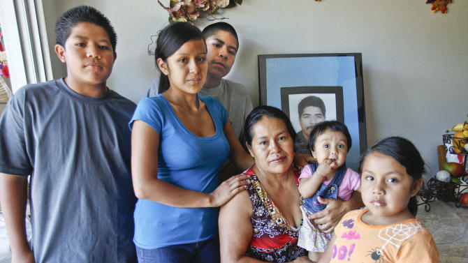 In this June 25, 2012 photo, Juana Garcia Martinez, seated center, poses with her family, from left, son Carlos, 12, daughter Gladys Dominguez, 19, son Victor, 19, granddaughter Jazleen Dominguez, 8-months, and daughter Katie, 5, in front of a photo of Juana Garcia's late husband, Ildefonso Martinez, in Vista, Calif.  Ildefonso Martinez died from dehydration trying to cross back into the United States after being deported last year. The death of migrants crossing the Southwest border has long been a tragic consequence of illegal immigration and, many say, the massive increase in U.S. border enforcement. For some, the tragedies are a powerful motivator in pushing Congress to act this year on a larger immigration reform package. (AP Photo/Lenny Ignelzi)