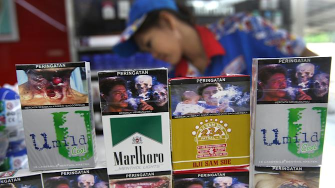 New packs of cigarettes displaying pictorial health warnings are arranged on the counter by a shop attendant for photographers at a convenience store in Jakarta, Indonesia, Tuesday, June 24, 2014. Tobacco companies on Tuesday largely snubbed an Indonesian law requiring them to put graphic photo warnings on all cigarette packs being sold, marking another setback in a country that's home to the world's highest rate of men smokers and a wild, wild west of advertising. (AP Photo/Tatan Syuflana)