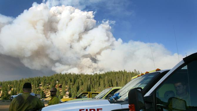 Crews at the base stand by as smoke rises from the Shingle Fire east of Cedar City, Utah, on Monday, July 2, 2012. Evacuations were ordered as the 500-acre wildfire that broke out Sunday threatened about 100 cabins inside Dixie National Forest. In all, 10 wildfires were burning Monday across Utah. (AP Photo/The Deseret News, Scott G Winterton)
