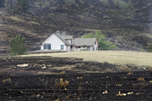 A house is surrounded by burned grass as a result of the High Park wildfire near Bellvue, Colo., on Monday, June 18, 2012. The wildfire has burned over 180 homes. (AP Photo/Ed Andrieski)