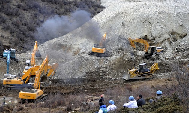 In this photo released by China&#39;s Xinhua News Agency, earthmovers remove rocks and mud on the scene where a landslide hit a mining area in Maizhokunggar County of Lhasa, southwest China&#39;s Tibet Autonomous Region, on Friday, March 29, 2013. The large landslide trapped dozens of workers in the gold mining area, state media reported. (AP Photo/Xinhua, Chogo) NO SALES