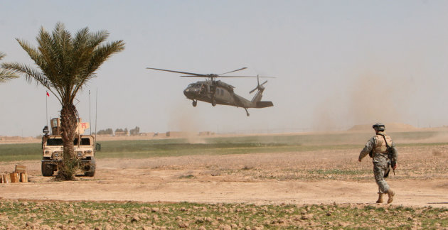 FILE - In this March 17, 2006 file photo, a U.S. helicopter lands in the field as a U.S. soldier stands guard outside Samarra, Iraq. The White House is planning to keep up to 10,000 troops in Iraq next year, despite opposition not only from Iraqis but also key Democratic Party allies who demand that President Barack Obama bring home the U.S. military as he promised as a candidate. (AP Photo/Khalid Mohammed, File)
