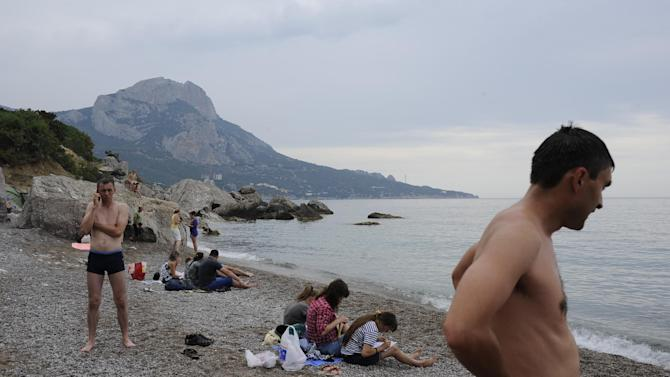 Russian tourists rest on the Black Sea beach about 35 km. (22 miles) from Yalta, Crimea, Sunday, June 15, 2014. When Russia annexed the Black Sea peninsula of Crimea earlier this year, it regained not only harbors for its navy and abandoned Ukrainian military bases but also long stretches of pebble beaches that were the summer destination of choice for millions of Soviet citizens. The Kremlin is hoping to attract tourists to Crimea, which Russia annexed in March, by asking state-controlled companies to send their employees on free vacation trips.(AP Photo/Andrew Lubimov)