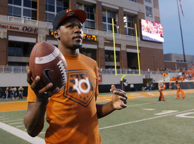 Oklahoma City Thunder's Kevin Durant, who attended the University of Texas, tosses a football around on the sidelines during the first quarter of an NCAA college football game between Oklahoma State a