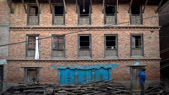 An earthquake victim exits his damaged house in Sankhu, on the outskirts of Kathmandu