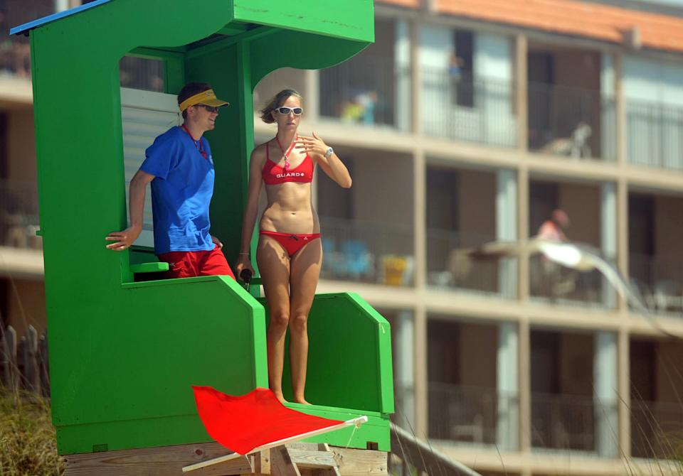 Lifeguards look over the water as strong rip currents created dangerous swimming conditions and prompted Carolina Beach, N.C. Ocean Rescue to close the beach to swimming and not allow people in past their knees on Saturday, May 26, 2012.    (AP Photo/The Star-News,Matt Born )