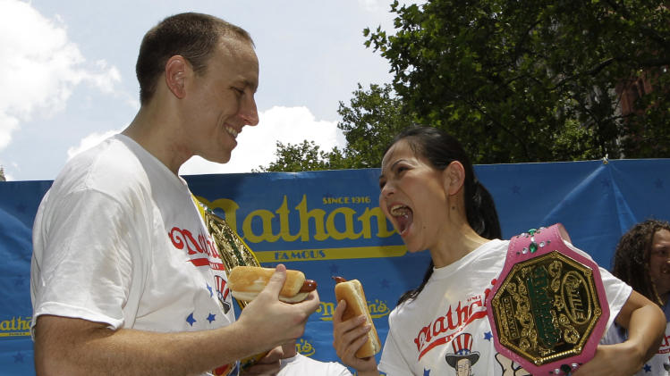 "Women's hot-dog eating record-holder, Sonya ""The Black Widow"" Thomas, right, challenges five-time hot-dog eating world champion Joey Chestnut, left, during a weigh-in for contestants in the annual Coney Island Fourth of July international hot-dog eating contest, Tuesday, July 3, 2012, at City Hall Park in New York.  The event will take place midday Wednesday, July 4, at Coney Island, Brooklyn.  Chestnut will try to break his own world record of downing 68 hot dogs and buns in 10 minutes.  Thomas, who weighs 100 pounds, will headline the women's competition, facing 14 female eaters from the U.S. and Canada. (AP Photo/Kathy Willens)"